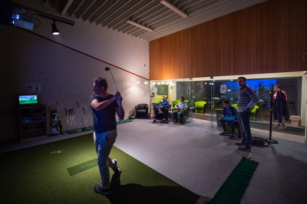 Schwungtraining im Golfsimulator vor Zuschauern.
